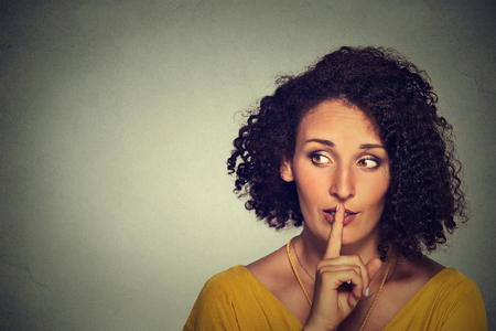Closeup portrait secretive young woman placing finger on lips asking shh, quiet, silence looking sideway isolated gray background. Human face expressions, sign emotion feeling body language reaction