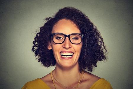 cabello rizado: Foto de cabeza de una mujer sonriente feliz en vidrios aislados en el fondo de la pared gris. Positivo expresión de la cara Foto de archivo