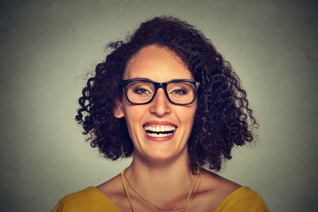 headshot: Headshot of a happy smiling woman in glasses isolated on gray wall background. Positive face expression