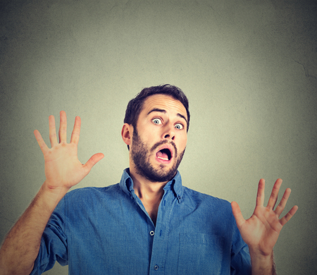 cowardly: scared man on gray wall background Stock Photo