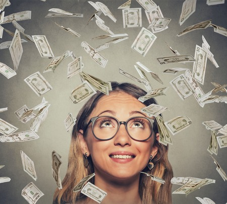 lottery win: Portrait happy successful young woman in glasses looking up under a money rain dollar bills banknotes falling down isolated on gray wall background with copy space Stock Photo