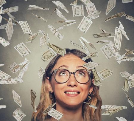 loteria: Retrato feliz mujer joven y exitoso en los vidrios que miran para arriba bajo una lluvia de dinero dólar facturas billetes que caen abajo aislado sobre fondo gris de la pared con el espacio de la copia Foto de archivo