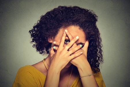 timid: Closeup shy woman hiding face timid. Cute young caucasian woman peeking though hands. Gray background.