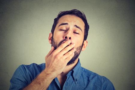 bored face: Man yawning isolated on gray background