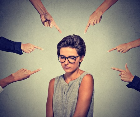 societies: Concept of accusation guilty shy person girl. Sad embarrassed upset woman in glasses looking down many fingers pointing at her isolated grey wall background. Human face expression emotion feeling