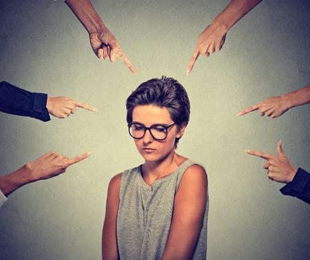 asustado: Concepto de acusaci�n de culpabilidad ni�a persona t�mida. Triste mujer molesta verg�enza en copas mirando hacia abajo muchos dedos apuntando a su aislada fondo de la pared gris. rostro humano emoci�n expresi�n sentimiento