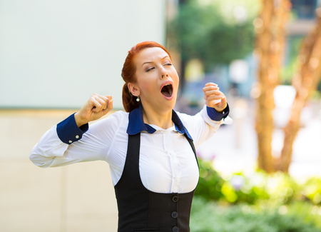 woman open mouth: It is too early for this meeting. Portrait sleepy young business woman with wide open mouth yawning eyes closed looking bored isolated outside corporate office background. Emotion face expression