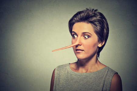 falsehood: Woman with long nose isolated on grey wall background. Liar concept. Human face expressions, emotions, feelings.
