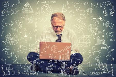 Älterer Mann, der an Computer arbeitet auf einem Fußboden sitzt in seinem Büro Bau zukünftige Geschäftsstrategie. Finanzen Wirtschaft Bildung Konzept. Datenverarbeitungsmanagement