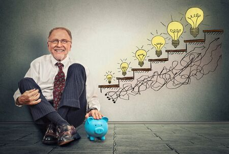 wall texture: Excited happy senior executive man sitting on a floor in his office with piggy bank celebrates business success, promotion, company growth isolated on gray wall texture background