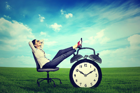 working hours: young business woman corporate executive relaxing sitting on a chair in the open air outdoors