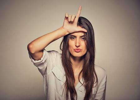 Nahaufnahmeportrait junge unglückliche Frau, die Verlierer Zeichen auf der Stirn, die Sie betrachten, Ekel im Gesicht isoliert auf grauen Wand Hintergrund. Negative menschlichen Gesichtsausdruck