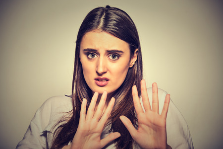 deny: Closeup portrait of scared woman raising hands up in defense afraid about to be attacked or avoiding unpleasant situation, isolated on gray background. Negative human emotion facial expression feeling