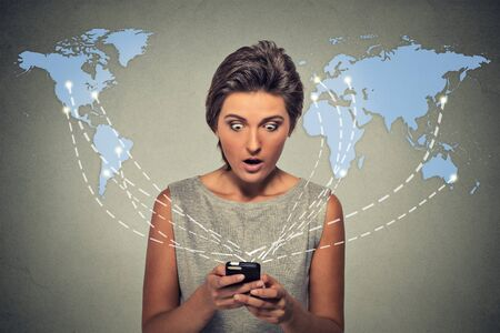 mobile internet: Modern communication technology mobile phone high tech, web connection concept. Shocked young woman holding using smartphone connected browsing internet worldwide world maps as a background. Stock Photo