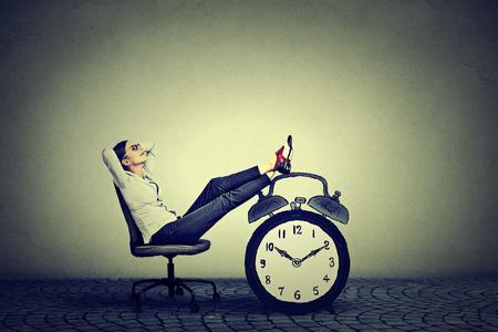 Glückliche junge Geschäftsfrau in ihrem Büro sitzen entspannend. Stress-freie Zeit-Management-Konzept