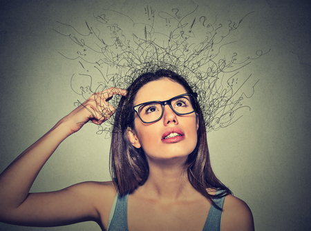 Closeup portrait young woman scratching head, thinking daydreaming with brain melting into lines question marks looking up isolated on gray background. Human facial expressions, emotion feeling sign