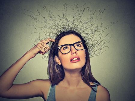 inteligencia: Retrato del primer mujer joven rascarse la cabeza, pensando soñando con el cerebro de fusión en las líneas de signos de interrogación mirando hacia arriba aislados en fondo gris. expresiones faciales humanas, emoción signo