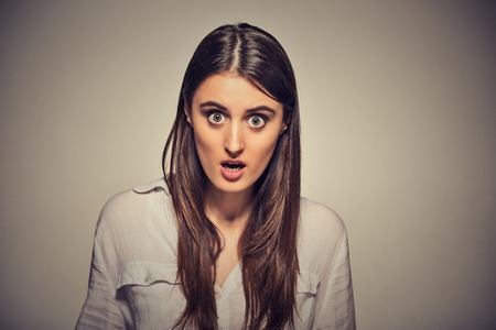 screaming face: Surprise astonished woman. Closeup portrait woman looking shocked in full disbelief wide open mouth isolated on grey wall background. Human emotion facial expression body language.