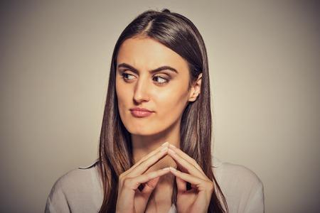 Nahaufnahmeportrait hinterhältig, schlau, intrigante junge Frau, die etwas Plotten auf grauem Hintergrund. Negative menschliche Emotionen, Mimik, Gefühle, Haltung
