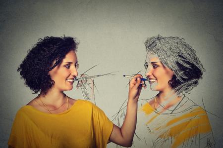 imagen: Cree usted mismo, su concepto de la imagen. Mujer joven atractiva que hace un dibujo, boceto de sí misma aislado en el fondo gris de la pared. expresiones faciales humanos, la determinación, la creatividad Foto de archivo