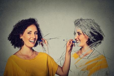 자신의 이미지 개념을 창조하십시오. 매력적인 젊은여자가 그림, 회색 벽에 격리 자신의 스케치 드로잉 벽 배경. 인간의 얼굴 표현, 결정, 독창성