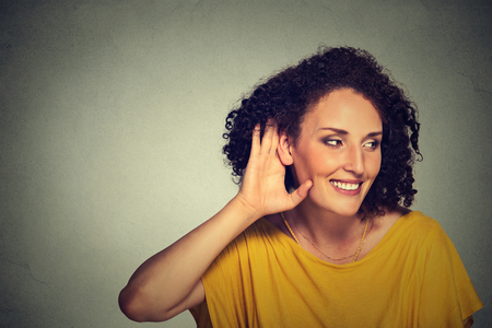 secretly: Closeup portrait happy middle aged nosy woman hand to ear gesture carefully secretly listening juicy gossip conversation privacy violation isolated on grey background. Human face expression Stock Photo