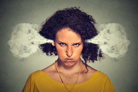 Closeup portrait of angry young woman, blowing steam coming out of ears, about to have nervous atomic breakdown, isolated gray background. Negative human emotions facial expression feelings attitude Stockfoto