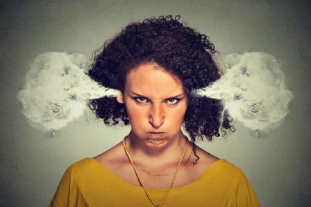 attitude: Retrato de mujer joven enojado, soplando vapor que sale de las orejas, a punto de tener descomposición atómica nervioso, fondo gris aislado. emociones humanas negativas expresión facial actitud sentimientos Foto de archivo