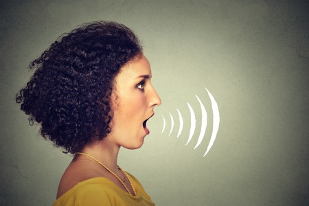 Side profile young woman talking with sound waves coming out of her mouth isolated on grey wall background. Human face expressions 스톡 콘텐츠
