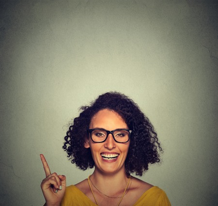 adult woman: Happy woman in glasses pointing up with her finger isolated on gray wall background