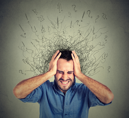 focus on: Stressed man upset frustrated has too many thoughts with brain melting into lines question marks. Obsessive compulsive, adhd, anxiety disorder. Negative human emotions face expression feelings Stock Photo