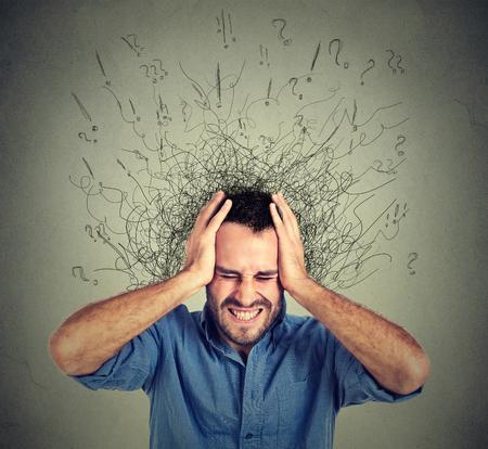 Zestresowany człowiek zdenerwowany sfrustrowany ma zbyt wiele myśli z mózgu wtapiając się linie znaki zapytania. Obsesyjno-kompulsywne, ADHD, zaburzenia lękowe. Negatywne uczucia ludzkie emocje ekspresyjne twarzą