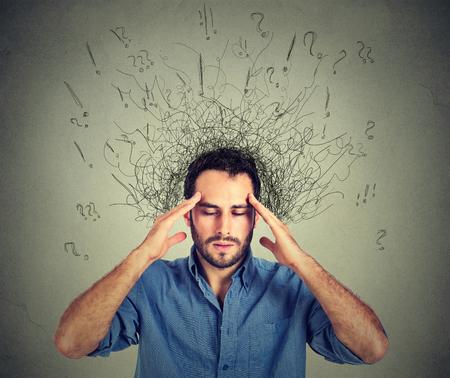 mente humana: hombre joven triste del primer con la expresión de la cara preocupada y estresada cerebro de fusión en las líneas de signos de interrogación. compulsivos, TDAH, trastornos de ansiedad obsesivo