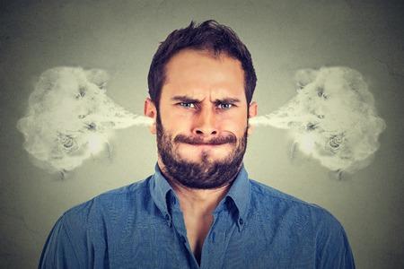 attitude: Primer retrato de hombre joven enojado, soplando vapor que sale de las orejas, a punto de tener descomposición atómica nervioso aislado fondo gris. emociones humanas negativas expresión facial actitud sentimientos