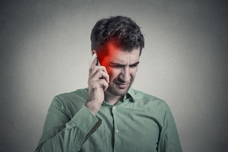 Man on the phone with headache. Upset unhappy guy talking on a phone isolated grey wall background. Negative human emotion face expression feeling life reaction. Cellular mobile radiation concept
