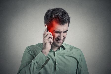 Man aan de telefoon met hoofdpijn. Upset ongelukkige man te praten over een telefoon geïsoleerd grijze muur achtergrond. Negatieve menselijke emotie gezicht gevoel leven reactie. Cellulaire mobiele straling begrip
