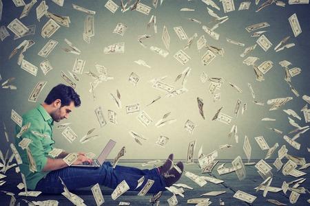Hombre joven con un ordenador portátil sentado en un negocio en línea edificio piso haciendo cuentas de dinero en efectivo en dólares que caen hacia abajo. lluvia de dinero. Principiante empresario de TI concepto de economía éxito