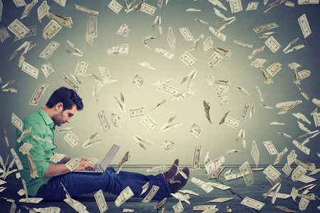 Jeune homme utilisant un ordinateur portable assis sur une ligne entreprise de construction de plancher faisant des factures d'argent en dollars cash tombant. pluie d'argent. Débutant entrepreneur IT concept d'économie de succès