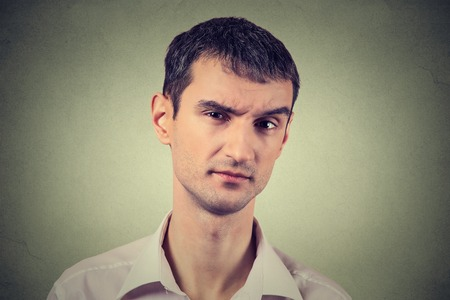 some: Closeup portrait of skeptical man looking suspicious, some disgust on his face mixed with disapproval isolated on gray background. Negative human emotions, facial expressions, feelings Stock Photo