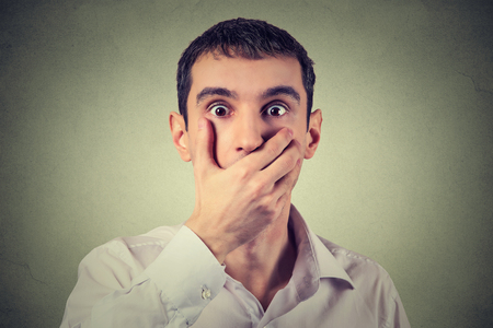 uptight: Closeup portrait of scared young man with hand over his mouth, stunned and speechless, isolated on gray wall background. Human face expression emotion feelings Stock Photo