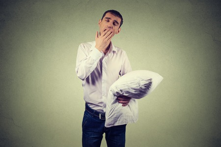 sleepiness: Handsome man yawning with a pillow in hand. Sleep deprivation, burnout, laziness concept