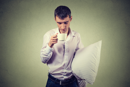 eyes opened: very tired, almost falling asleep business man holding a cup of coffee and pillow struggling not to crash and stay awake, keeping his eyes opened, isolated on gray background Stock Photo