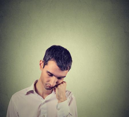 depresión: Retrato de detalle de un hombre triste, deprimido, solo, decepcionado con la cabeza apoyada en la mano mirando hacia abajo aislado sobre fondo gris de la pared con el espacio de la copia