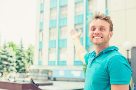 selling house: Handsome young man pointing in direction of apartment. New apartment in tall building