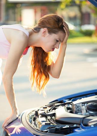 Betonte, verärgert junge Frau, die vor ihrem Auto gebrochen Auto mit geöffneter Motorhaube an Motor, außerhalb Straße, Straße suchen. Negative Gesichtsausdrücke, Emotionen, Gefühle. Pech, Zitrone Auto Standard-Bild