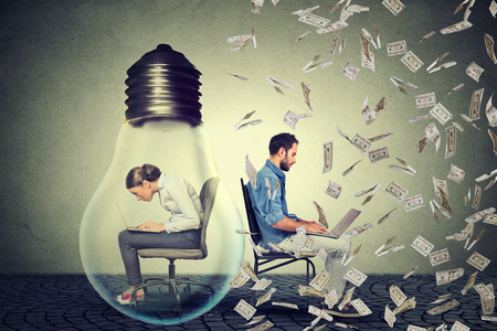 Woman sitting inside electric lamp using working on computer in corporate office next to young entrepreneur man under money rain. Company employee vs startup concept. Pay compensation difference idea Stock Photo