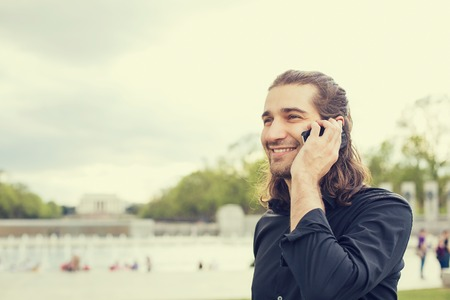 using phone: Closeup portrait happy young man talking on mobile phone Stock Photo