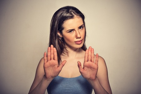 actitud: retrato de joven mujer enojada molesto del primer con mala actitud haciendo un gesto con las palmas hacia afuera para detener aislados sobre fondo gris de la pared. cara emoci�n negativa lenguaje corporal sensaci�n expresi�n humana