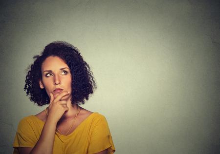 Vrouw denken dromen heeft veel ideeën te kijken die op grijze muur achtergrond.