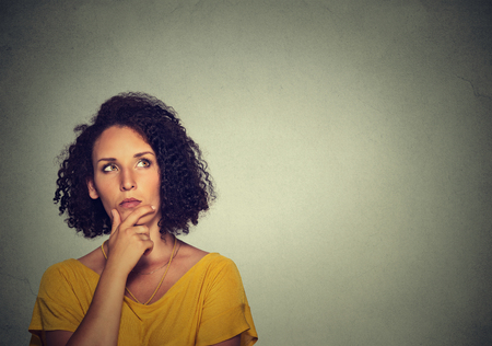 ideas problems: Woman thinking dreaming has many ideas looking up isolated on gray wall background.
